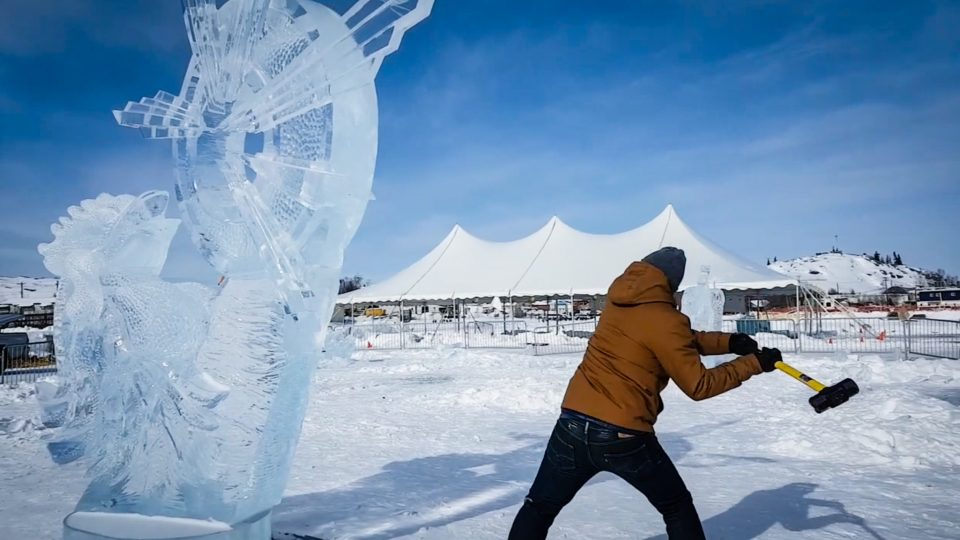 A Yellowknife resident takes a sledgehammer to an ice carving on the site of the 2018 Long John Jamboree