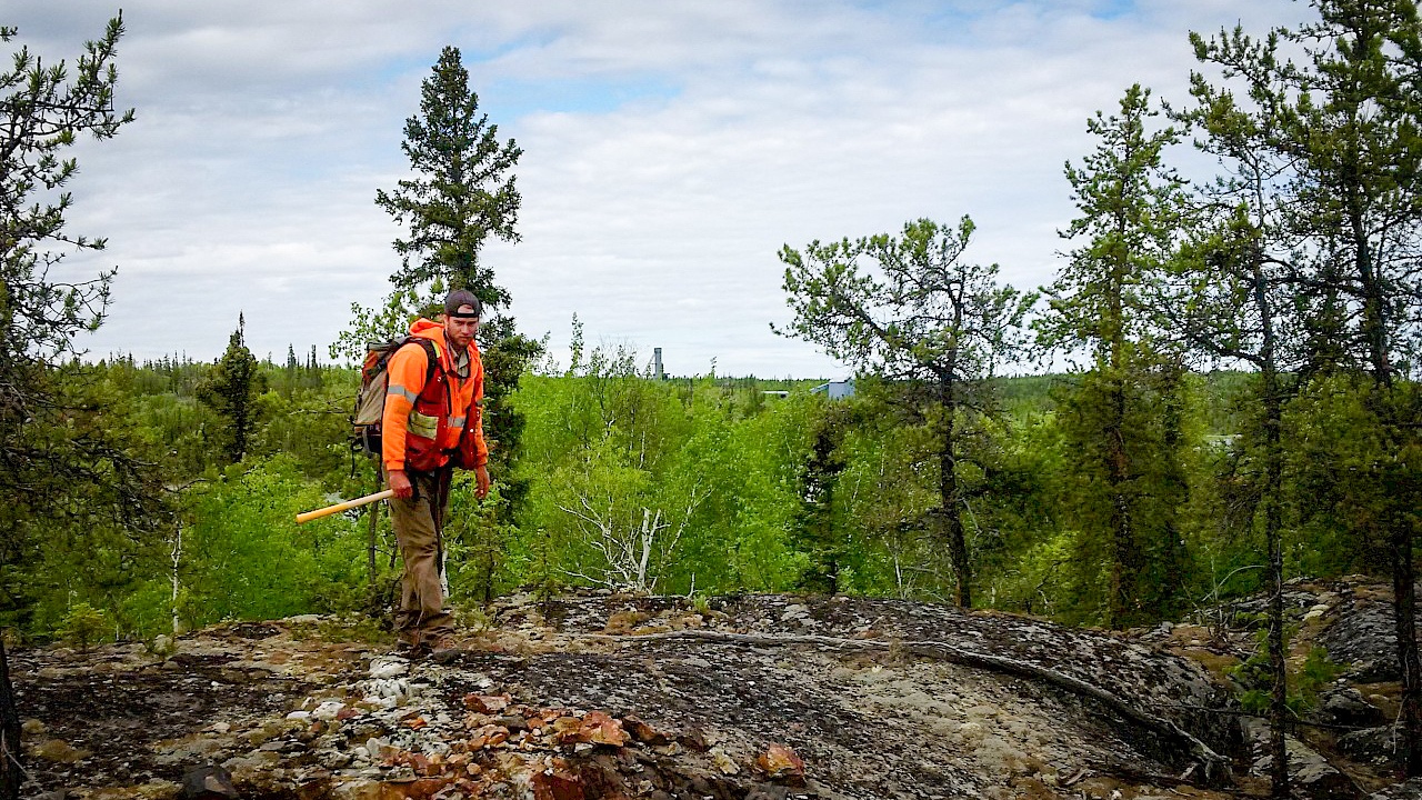 A worker stands above a mineralized vein near the former site of the Tom Mine north of Yellowknife - TerraX