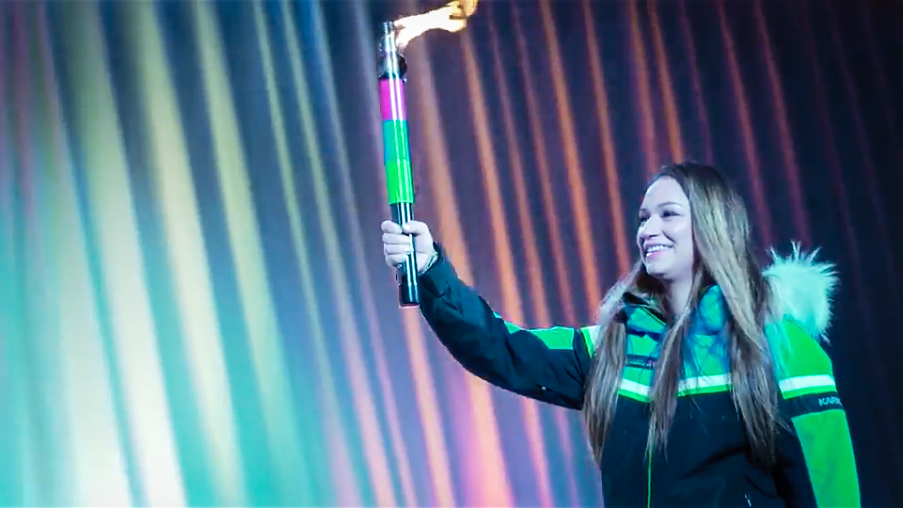 Arctic sports athlete Veronica MacDonald, from Fort Smith, carries the flame into the 2018 Arctic Winter Games opening ceremony - AWG