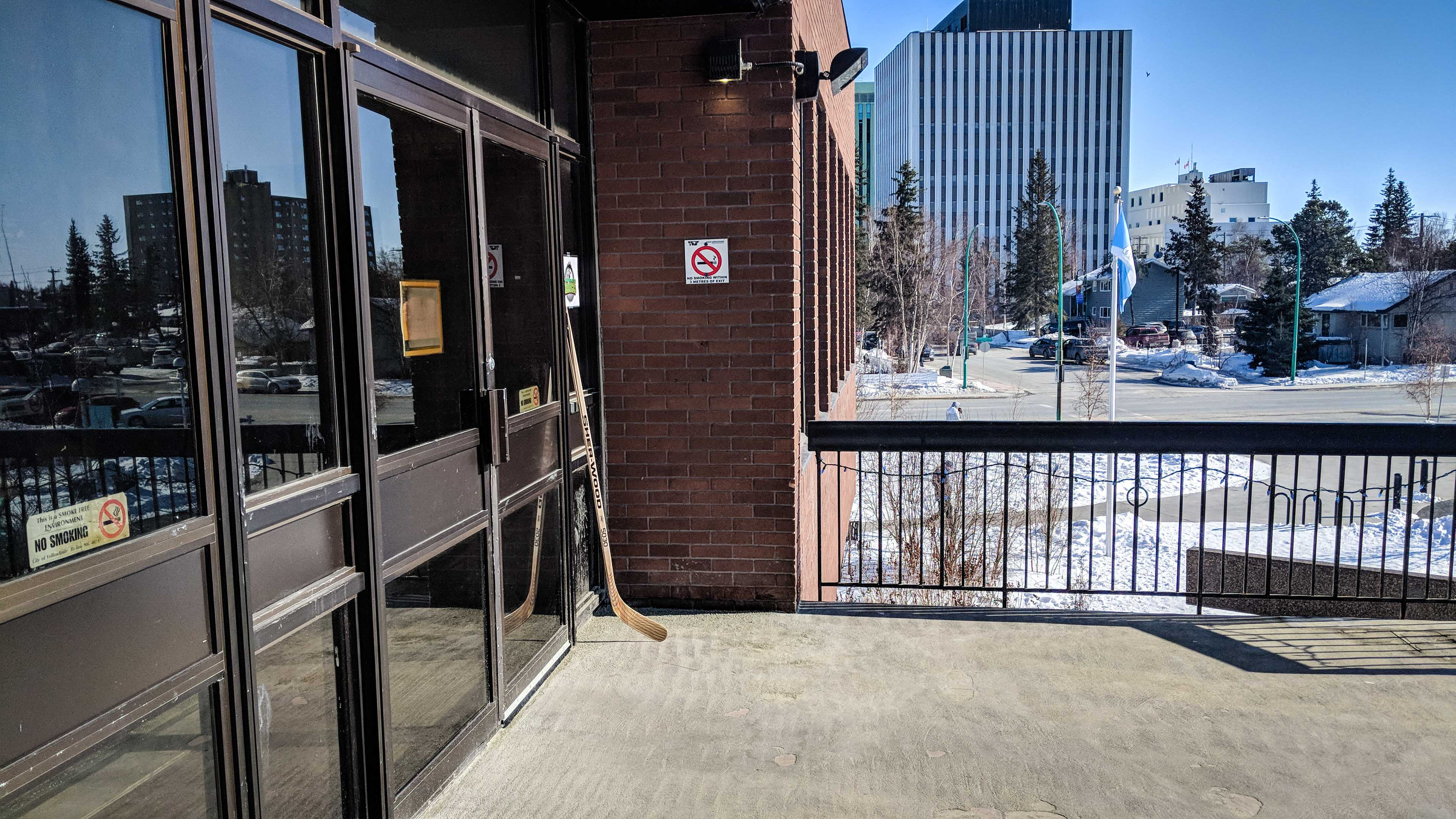 A hockey stick rests outside the doors of Yellowknife's City Hall on Tuesday, April 10, 2018, in memory of those killed in the Humboldt Broncos bus disaster