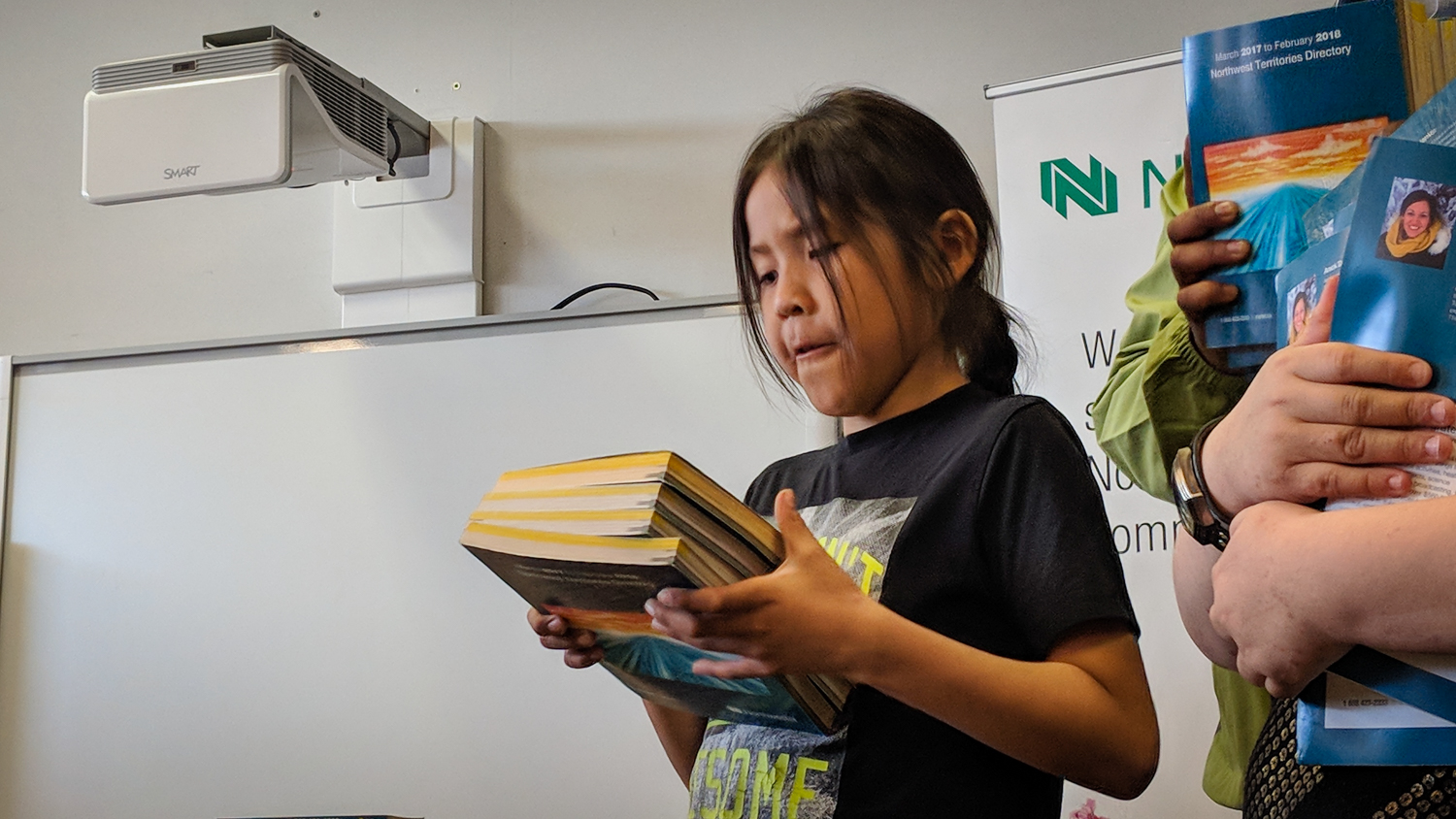 A Mildred Hall School student studies a collection of Northwestel telephone directories at a photo call in May 2018
