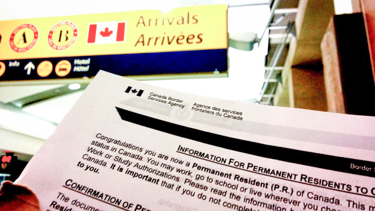 A file photo of permanent residency paperwork being held at Calgary Airport