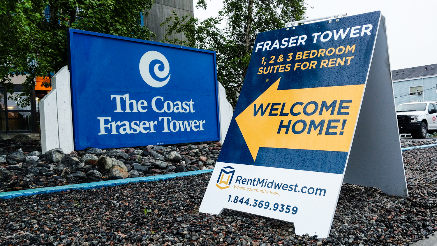 A sign advertising apartments for rent sits beside the Coast Fraser Tower hotel