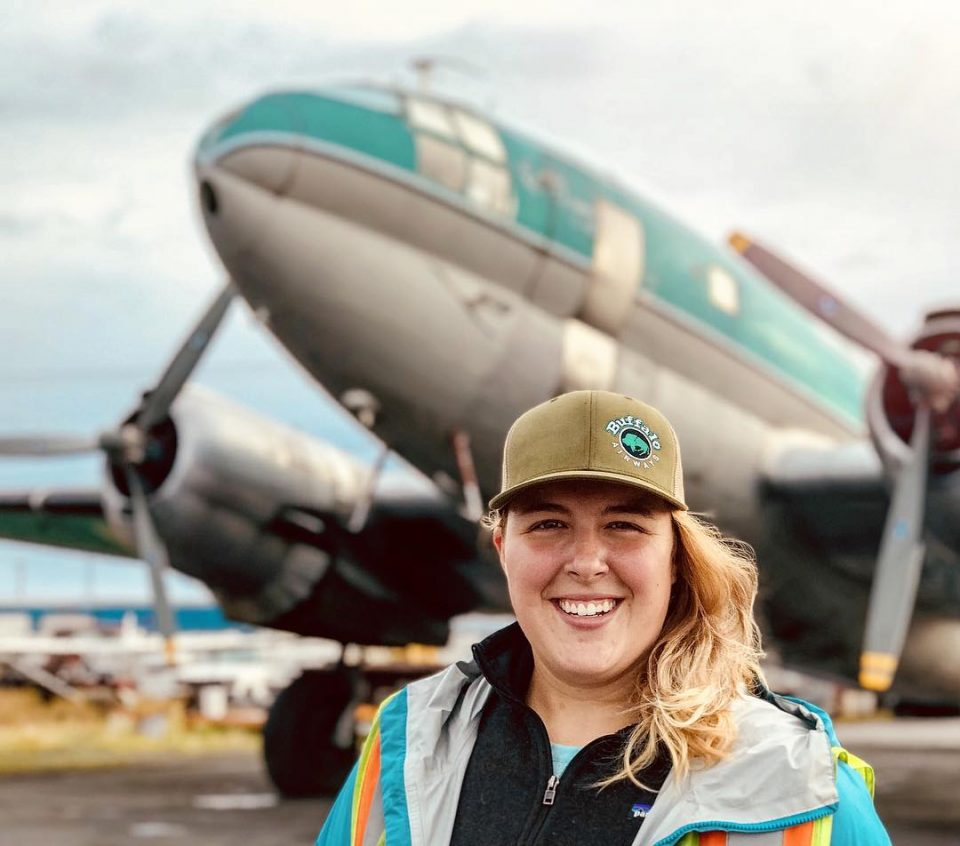 Jamie MacDonald stands in front of a Buffalo Airways Curtiss C-46 transport aircraft