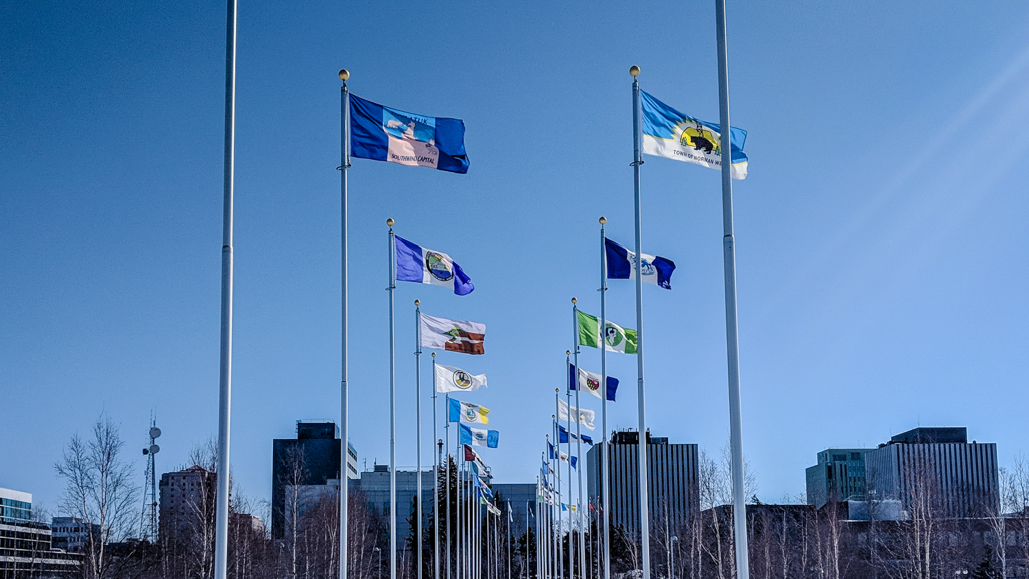A file photo shows the flags of various NWT communities flying in Yellowknife