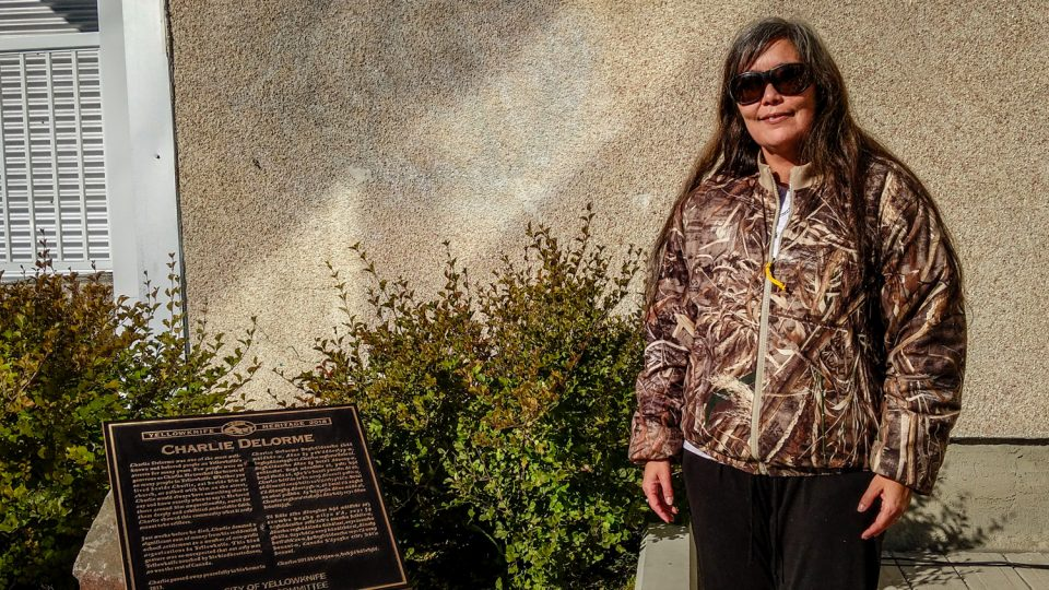 Nadine Delorme poses alongside a plaque dedicate to her uncle, Charlie