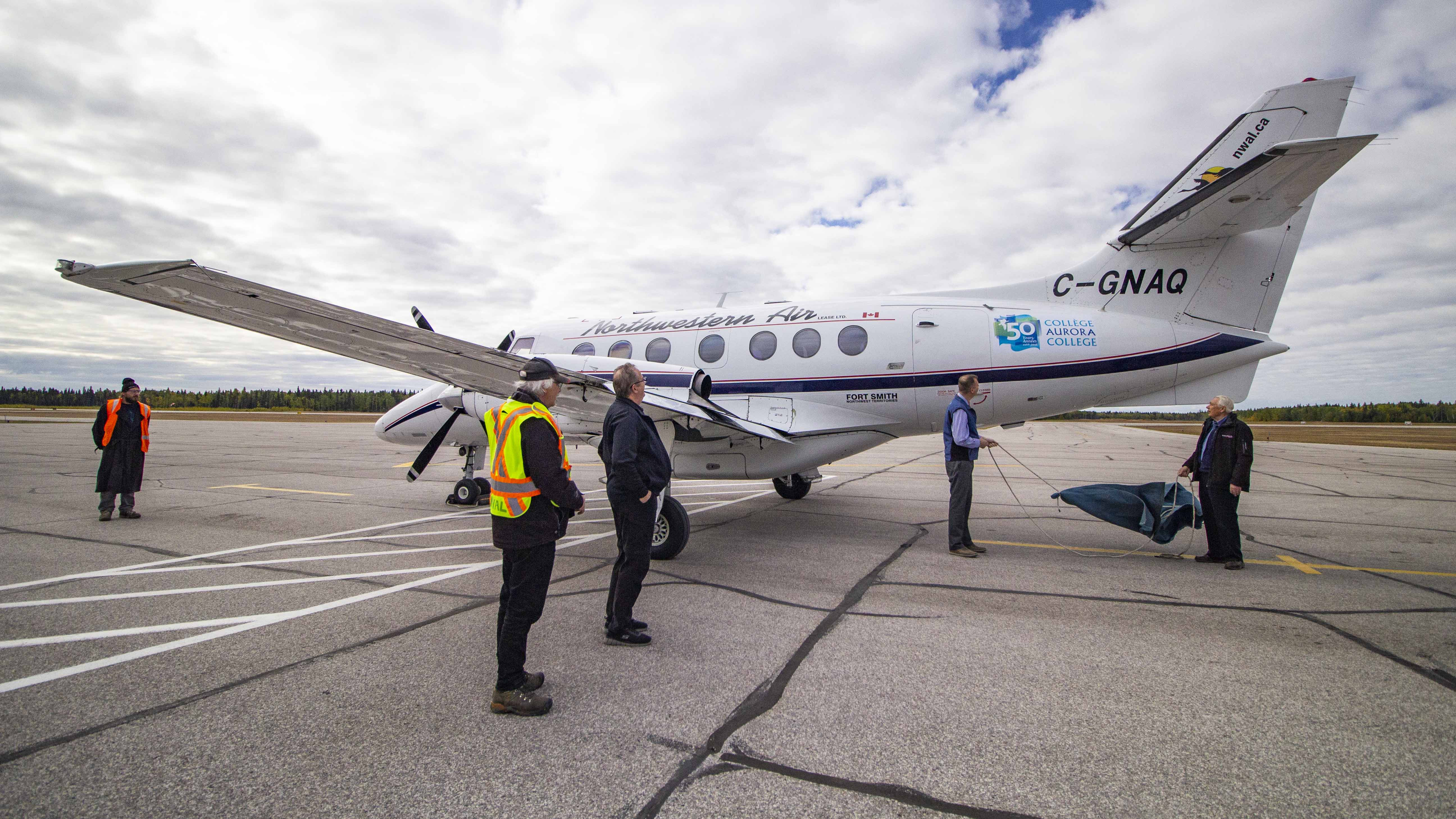 Terry Harrold, president and founder of Northwestern Air Lease, far right, and Jeff O'Keefe, interim president of Aurora College, reveal the college's 50th anniversary logo on Jetstream as other Northwestern employees look on. Sarah Pruys/Cabin Radio