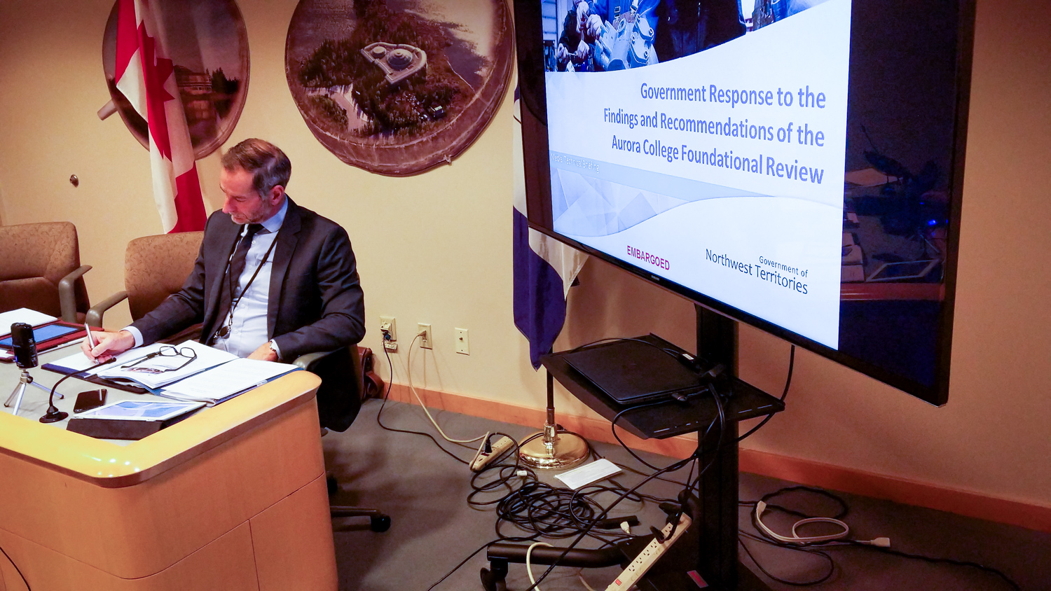 A senior territorial education official prepares next to a presentation relating to the NWT's plans for a polytechnic university on October 26, 2018