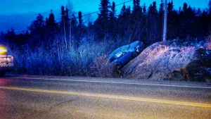 A vehicle is seen beached on a rockface on the highway leading into Yellowknife