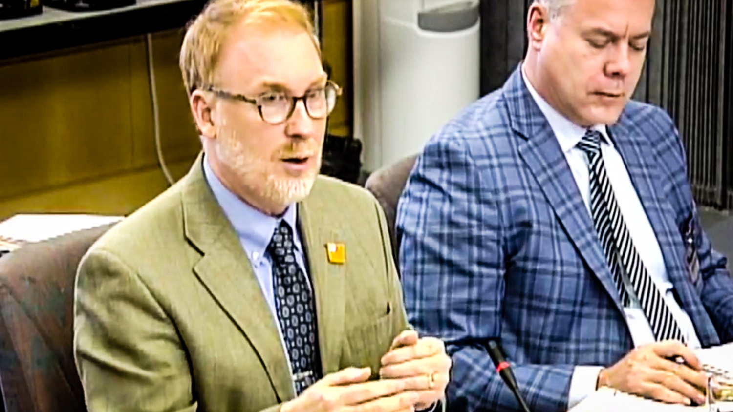 Deputy Minister of Health and Social Services Bruce Cooper, left, fields questions from MLAs on December 12, 2018, as seen via a live webcast