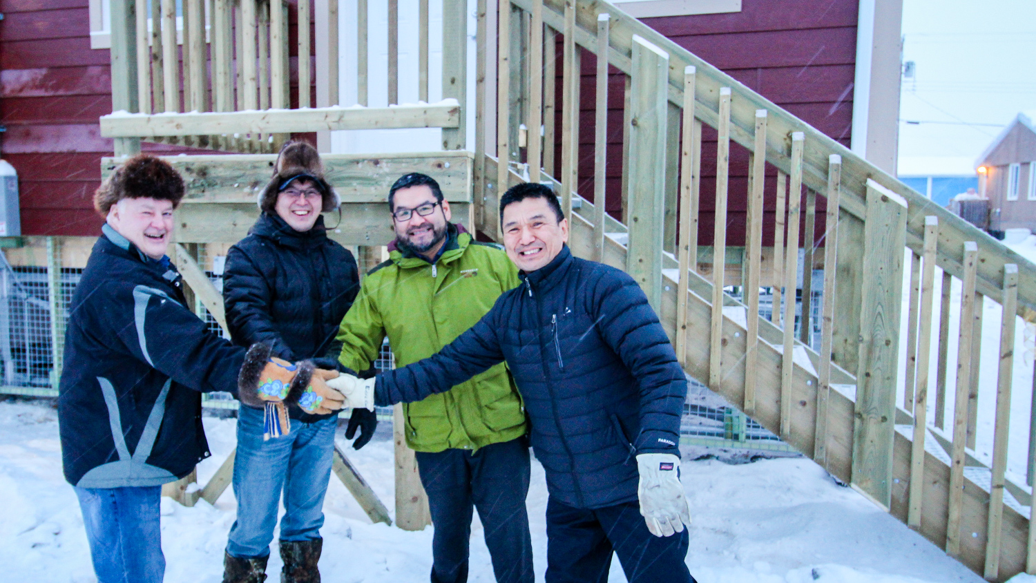 NWT Housing Corporation chief executive Tom Williams, MLA Sonny Blake, housing minister Alfred Moses, and Aklavik Indian Band Chief Eddie Greenland pose outside a new housing complex in Aklavik