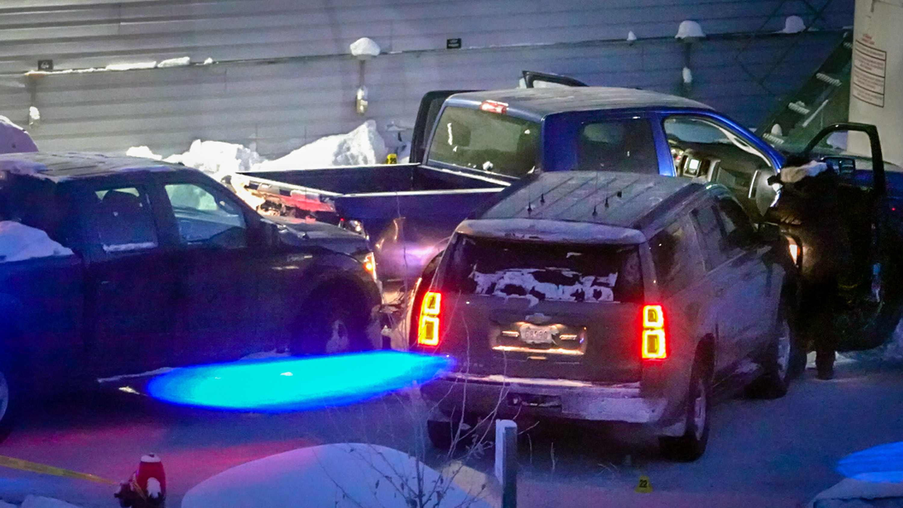 An RCMP officer inspects a blue pickup truck after a collision in a Yellowknife parking lot in January 2019