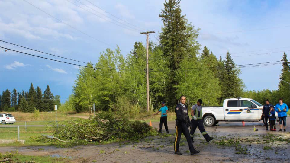 Police officers inspect damage caused by the apparent Fort Smith tornado