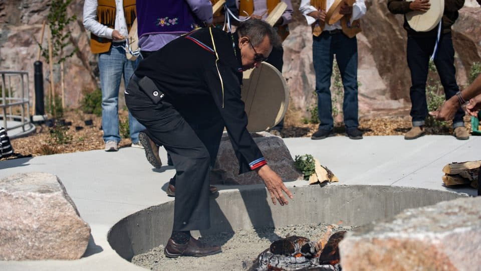 Felix Lockhart feeds the fire feeding at the opening of the new Stanton Territorial Hospital in July 2019. Sarah Pruys/Cabin Radio