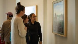 """Attendees chat about a painting by Behchokǫ̀'s Louis Angus Beaulieu called """"Circle of Wellness,"""" at the opening of the Stanton Territorial Hospital. Sarah Pruys/Cabin RadioSarah Pruys/Cabin Radio"""