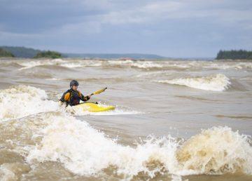 A kayaker surfs the Mountain Portage Rapids during Slave River Paddlefest 2019. Sarah Pruys/Slave River Paddlefest