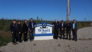 Dignitaries stand in front of welcome to Whati sign on August 24 2019