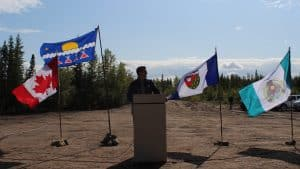 MLA Jackson Lafferty standing in front of Canad, Tlicho, NWT, Whati flags at ground breaking ceremony in Whati August 24 2019