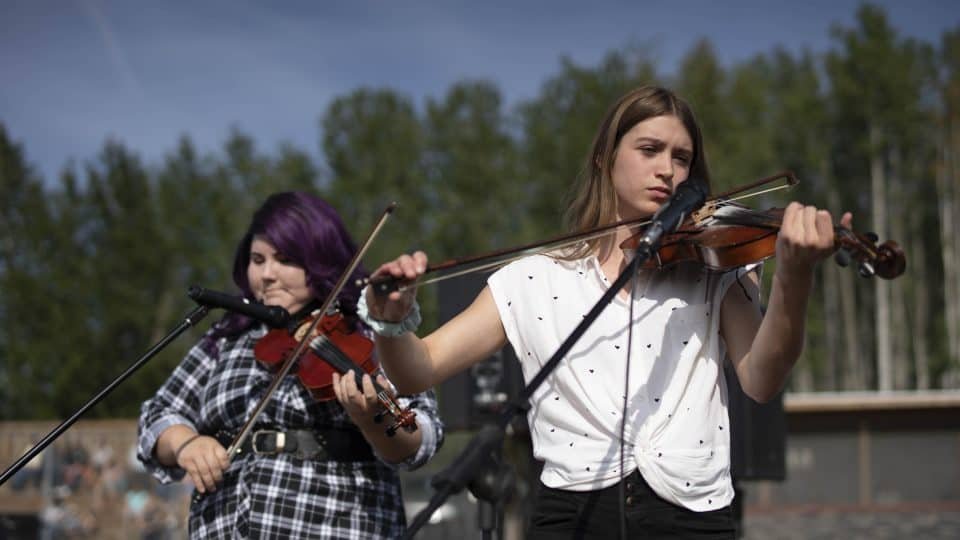 Members of the Kole Crook Fiddling Association play at the RCMP Musical Ride. Sarah Pruys/Cabin Radio