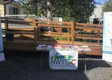 Table with books in between two banners at the NWT Literacy Council announcement for the Canada Learning Bond awareness program on August 27 2019