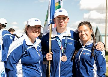 Team NT closing ceremony flagbearer Cameron Courtoreille, centre, with his Western Canada Summer Games bronze medal
