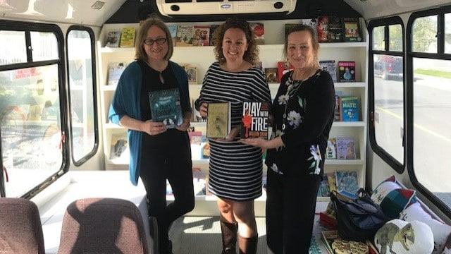 Rachel Vander Veen, Mayor Rebecca Alty and Minister Caroline Cochrane pose with books in the NWT Literacy Council new literacy bus at their announcement on August 27 2019
