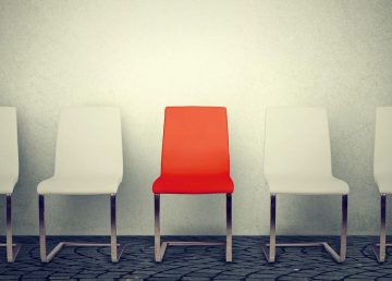 An empty orange chair sits among other chairs in a stock image