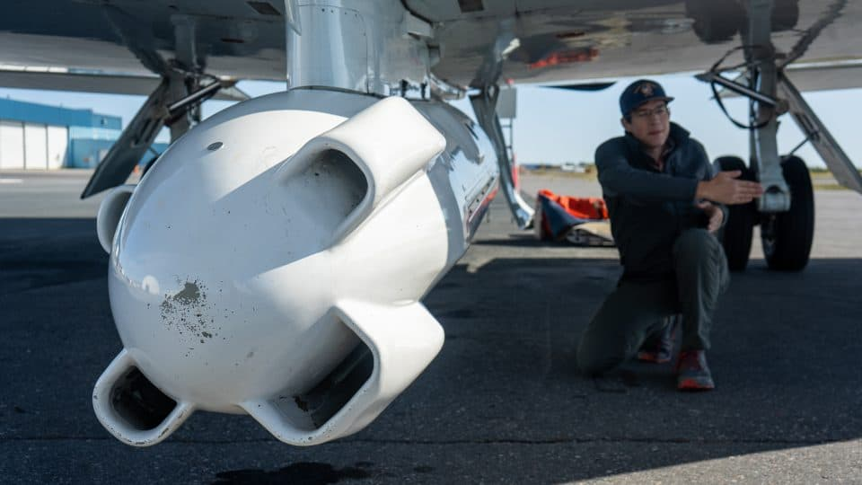 Systems engineer David Austerberry showcases the radar module mounted beneath the aircraft
