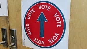 A sign directs voters toward a polling station in a school gym. Sarah Pruys/Cabin Radio