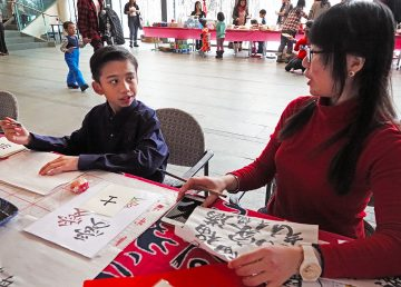 Kong Shu Ling, on a work tourist visa from Malaysia, shows Geruz Rodriguez, 10, how to do lettering.