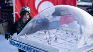 A child plays hockey foosball at Hockey Day in Canada at Somba K'e Park in Yellowknife. Sarah Pruys/Cabin Radio