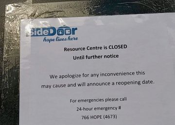 A sign on the door of Yellowknife's SideDoor resource centre announces its closure