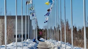 A person sits at the foot of flagpoles bearing the flags of NWT communities near Yellowknife's Frame Lake in April 2020