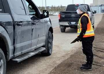A public health officer in a mask talks to a driver at a checkstop in Yellowknife in April 2020
