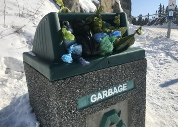 A garbage can at the foot of Tin Can Hill overflows with bags of dog poop