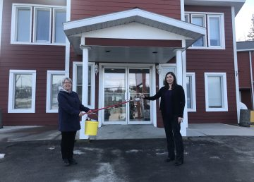 Kathy Yurris, property manager with TC Group of Companies, hands the keys to the Arnica Inn to Bree Denning, executive director of the Yellowknife Women's Society