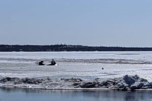 A snowmobile is stuck in the Dettah ice road off School Draw Avenue in May 2020. Sarah Pruys/Cabin Radio