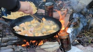 Lake Trout is fried up for a shore lunch. Sarah Pruys/Cabin Radio