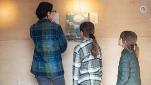 Sarah Swan and her children, Lucy and Nora, hang art in the YK ARCC's mobile gallery before opening the gallery to Peace River Flats families in May 2020.