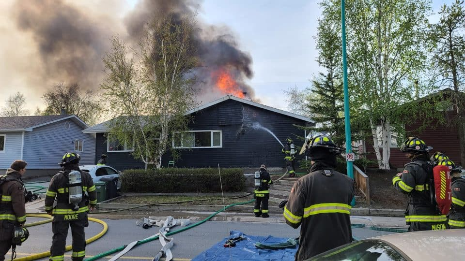 Flames emerge from the roof of a home on fire on Yellowknife's 50A Avenue