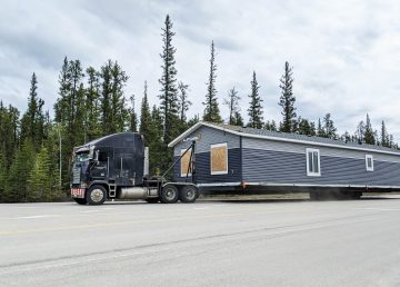 A truck carrying modular home turns off Highway 1 onto Highway 3 on June 5, 2020. Sarah Pruys/Cabin Radio