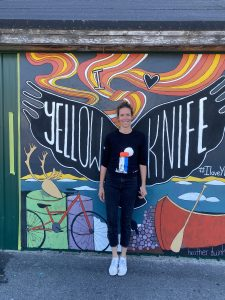 Heather Duinker in front of the finished I Love YK mural outside Weaver and Devore