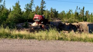A vehicle lies upside-down on a rock bed near Highway 3 following a rollover early on August 30, 2020