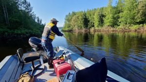 Bobby Norwegian steers his river scow into a creek east of Fort Simpson in August 2020