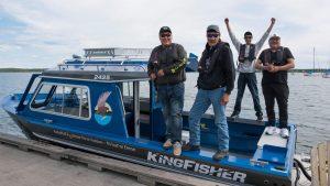 In July 2020, Ni Hat'ni Dene Gaurdians, left to right, Chase Lockhart, Joseph Catholique, Denecho Catholique, and Jason Michel prepare to take chart plotter training for a new boat. Photo: Pat Kane
