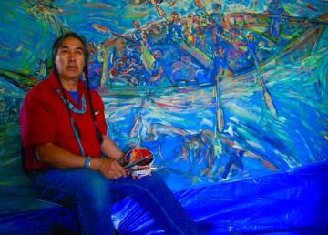 Antoine Mountain seen in front of his mural of a moosehide boat