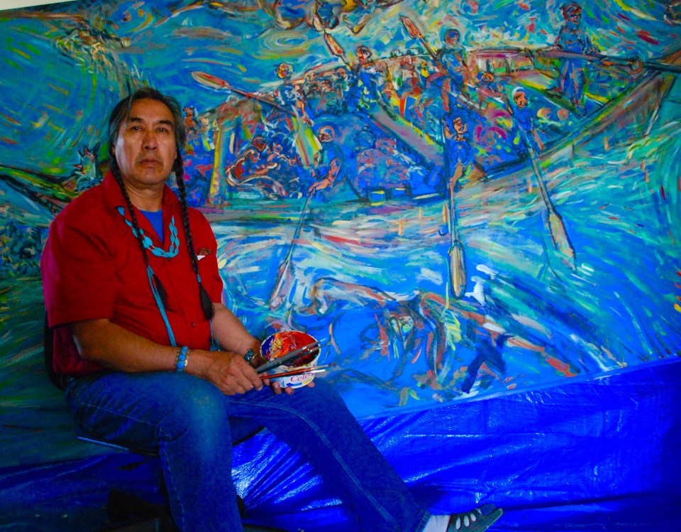 Antoine Mountain seen in front of his mural of a moosehide boat