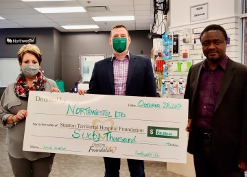 Stanton Territorial Hospital Foundation executive director Patty Olexin-Lang, left, and board member Marisa Ziyapapa, right, receive a cheque from Paul Gillard, Northwestel vice-president of business markets
