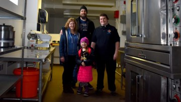 Volunteers Sarah and Dustin Nichol, left, with Alexander Pryor, right, and his daughter Lorelai, unloaded the truck of donated food in Fort Smith