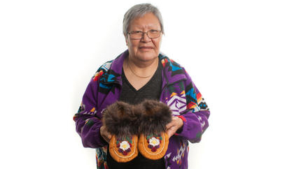 Lucy Simon holds a pair of moosehide tufted moccasins in an NWT Arts headshot.